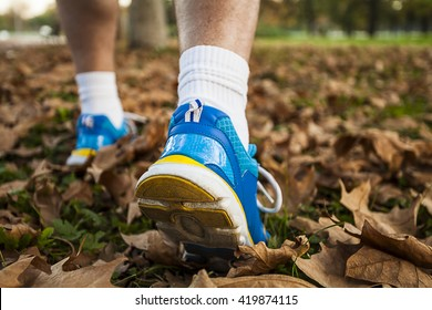 Middle-aged man in running shoes foliage walking