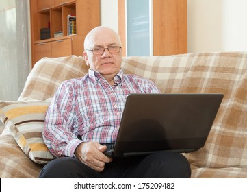 middle-aged man sitting on  couch with  laptop