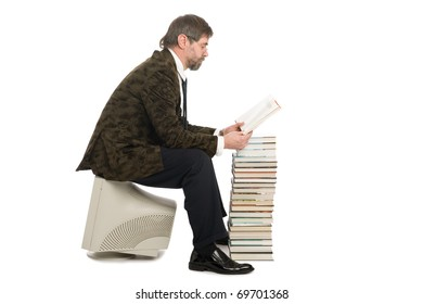Middle-aged man sitting on an old monitor and reads a book. Book instead of a computer.