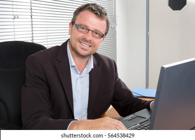 middle-aged man smiling at his desk with his glasses