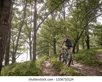 A middle-aged man in sportswear is riding a fat bike along forest paths. On the street is a good summer warm weather. The cyclist has a good figure and trained muscles.