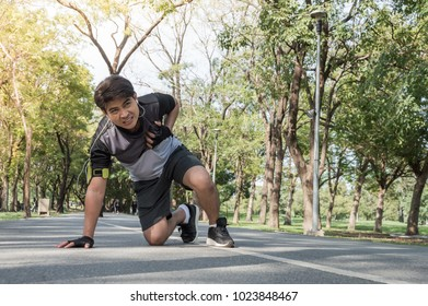 The middle-aged man suffering Chest pain while jogging exercise on a concrete road in a shady park.