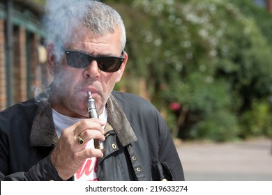 Middle-aged man in sunglasses puffing on an e-cigarette as he stands outdoors in the forecourt of a building with trees behind him and copyspace