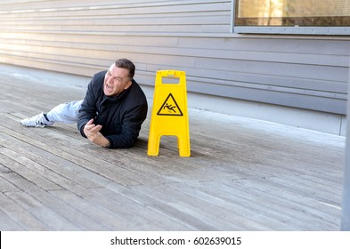 Middle-aged man taken a fall on a slippery floor right alongside a portable yellow warning sign grimacing in pain with lateral copy space