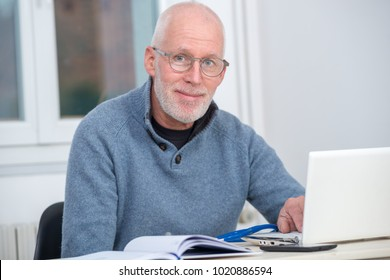 a middle-aged man using laptop in his office