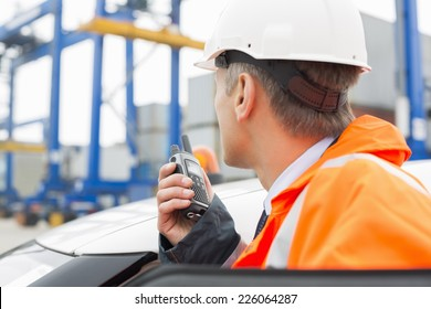 Middle-aged man using walkie-talkie while standing beside car in shipping yard