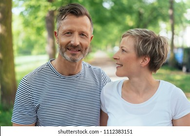 Middle-aged man walking through a park with his wife looking at the camera with a friendly smile as she turns to watch him