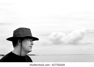 Middle-aged man wearing a hat looking out at the sea.