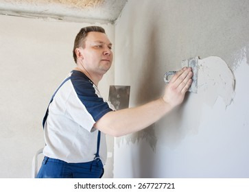 middle-aged man worker in blue trousers and gray t-shirt putting plaster on the wall with two trowels