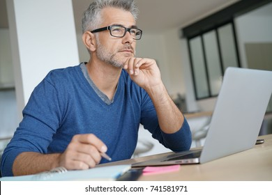 Middle-aged man working on laptop- thoughtful look