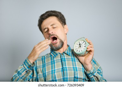 middle-aged man yawning with an alarm clock, isolated in studio on a background