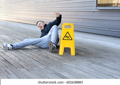 Middle-aged man yelling out in pain after falling on a slippery wooden deck right next to a bright yellow warning sign, with copy space to the side