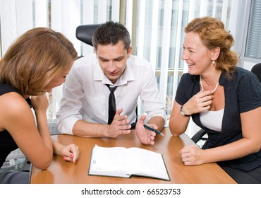 Middle-aged manager man sitting in board room Hi Res with his colleagues and explaining his view to certain business projects. Red-haired lady big happy laughing at him.