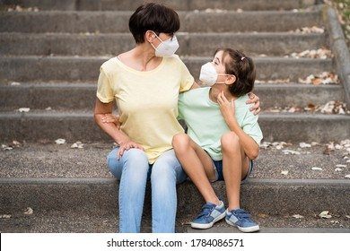 Middle-aged mother and daughter sit on the street wearing masks because of the Covid-19 pandemic