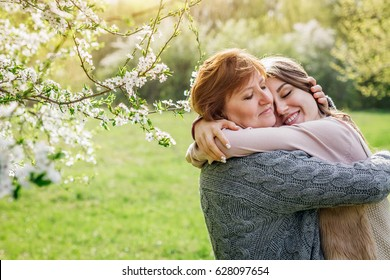 Middle-aged mother and her daughter hugging in blooming spring garden. Mothers day