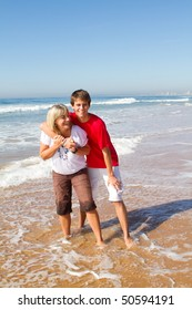 middle-aged mother and teen son playing on beach