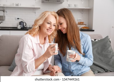 Middle-aged mother and young daughter together at home weekend holding cups drinking hot tea hugging smiling happy