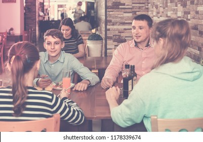 middle-aged parents and children chatting during dinner in comfortable family cafe