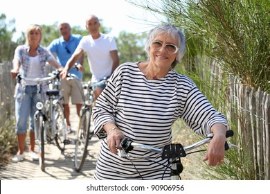 Middle-aged people on bike ride at the beach