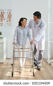 Middle-aged physiotherapist wearing white coat helping his senior patient to use front-wheeled walker while standing at modern office