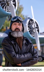Middle-aged pilot, posing in front of a classic plane