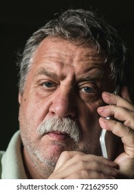 middle-aged sad caucasian man calling by smartphone