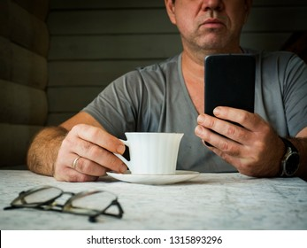 Middle-aged sad man using smartphone at home and drinking coffee