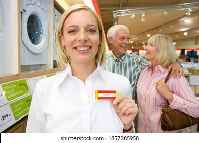 Middle-aged saleswoman holding up her name tag attached to her shirt while a senior couple is looking to buy a new washing machine in the background