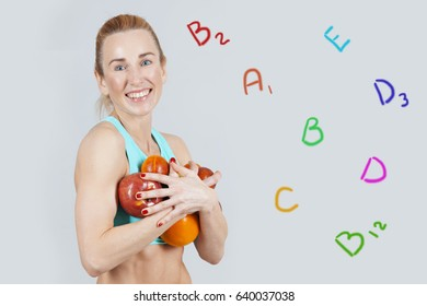 middle-aged smiling athletic woman holding apples in the hands and signs of vitamins near her on the grey background