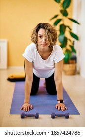 A middle-aged smiling pregnant woman kneeling on a yoga mat and doing fitness exercises at home.