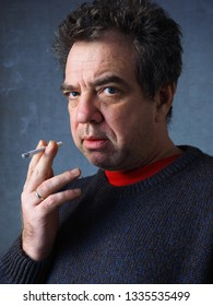 Middle-aged smoking man close-up indoor portrait