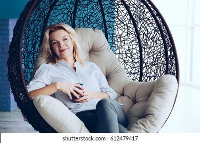 Middle-aged Stylish woman relaxed with cup of tea on modern home and sitting on bubble chair