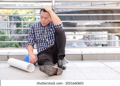 Middle-aged unhappy asian businessman unsuccessful that feeling down or disappointed about job sitting outside office , business man fired from job, businessman unemployed, Unemployment concept