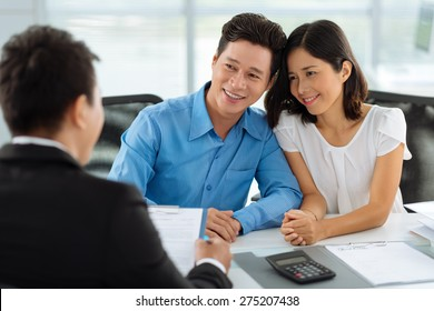Middle-aged Vietnamese family having consultation with real estate agent
