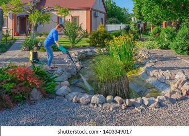 middle-aged white woman cleans a garden pond with high-pressure wash from sludge.