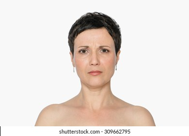Middle-aged woman with aging singes and problems, double chin, worry wrinkles, nasolabial folds. Natural look. Isolated, with copy space.