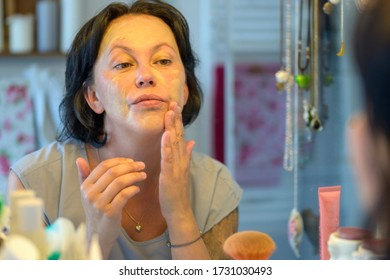 Middle-aged woman applying a face mask to her skin in her bathroom in an over the shoulder view with focus to her reflection in a mirror