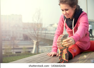 middle-aged woman athlete girl warm up stretching her hamstrings, leg and back.