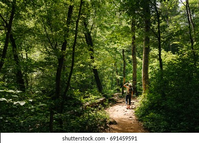 middle-aged woman with a backpack and wearing a hat walks along a forest path. The man on the walk is illuminated by the sun.
