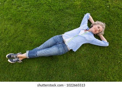 Middle-aged woman in casual weekend clothing relaxing on green grass in a park or yard. She is smiling with a happy, contented expression and looks like she is daydreaming. People enjoying nature.