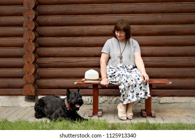 middle-aged woman in a countryside sitting on a wooden bench and looking at a black schnauzer near a log house