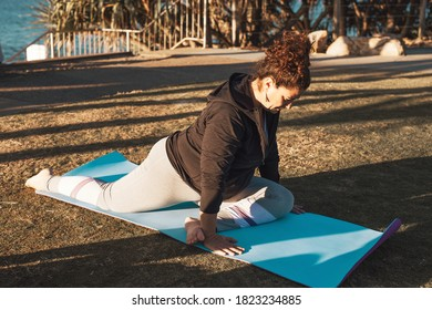 Middle-aged woman doing stretching in the city park on sunset. Female in yoga asana on mat