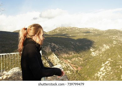 A middle-aged woman, dyed hair, a sweater and a scarf, stands on a viewing platform in the mountains