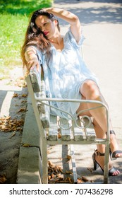 A middle-aged woman of European appearance with long dark hair in a summer dress is resting in the city's park. A woman a little overweight without complexes