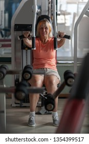 A middle-aged woman goes in for fitness, practicing on a training machine