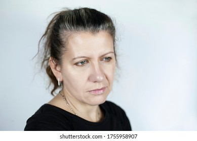 Middle-aged woman with graying hair on a light background looks away and misses her youth. The concept of anti-aging. Copy space