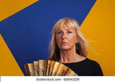 Middle-Aged Woman Having A Hot Flash, Holding a Fan