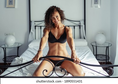 Middle-aged woman in her 40s in lingerie posing on the bed