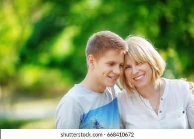 A middle-aged woman and her son teenager are smiling at each other in the park.