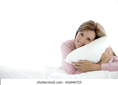 Middle-aged woman holding a pillow on a bed